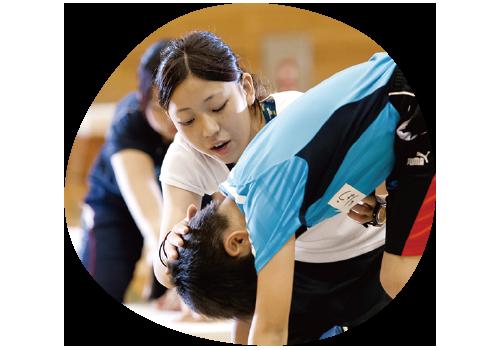 子どもの運動を補助する学生